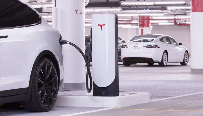 A Tesla Model X is shown at a Supercharger recharging station in a parking garage.