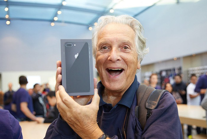 An excited customer holds a new iPhone 8 Plus on the day of the iPhone 8 launch