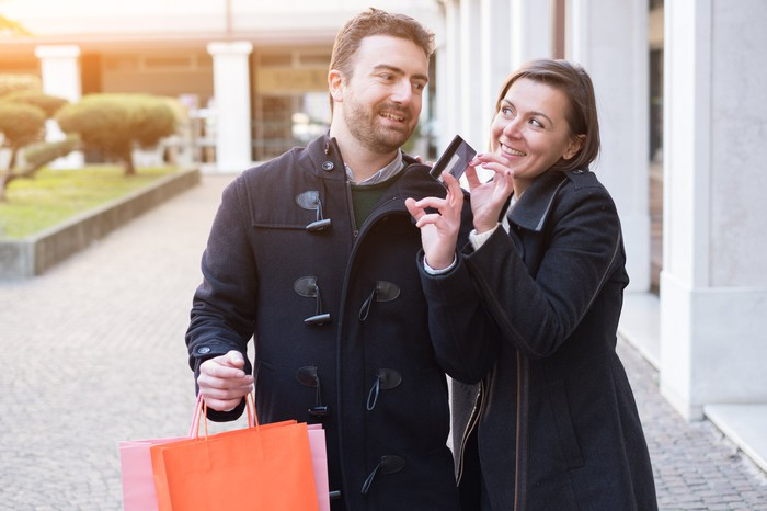 young couple shopping with both hands on a credit card