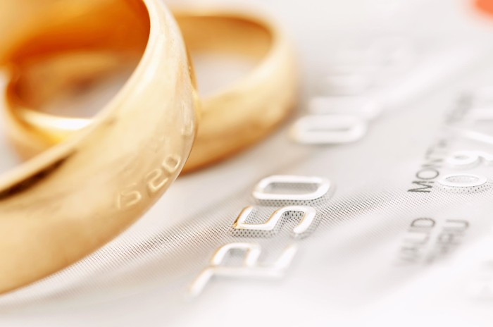 two gold wedding rings resting on part of a credit card