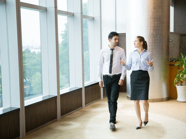 Businessman and Businesswoman Walking By Window in Discussion