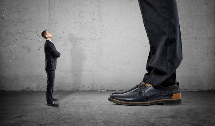 A small man in a suit looks up at a giant, whose feet and lower legs only can be seen.