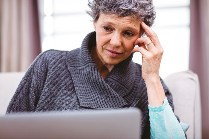 mature woman looking at laptop computer with raised eyebrows and thinking