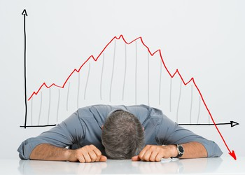 Man lying flat in front of a chart that points downward