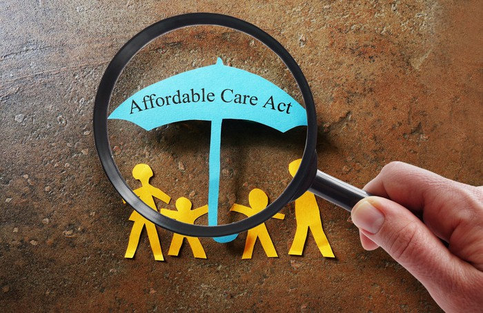 A person holding a magnifying glass looks at paper cut-outs of a family holding an umbrella that reads affordable care act.