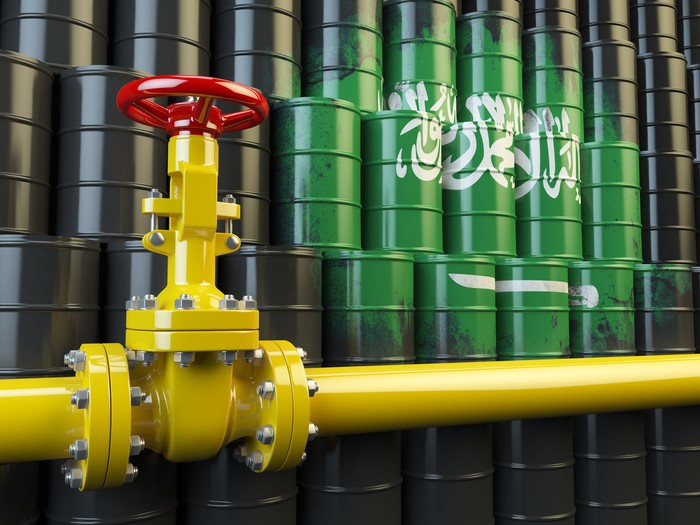 An oil pipeline valve in front of the Saudi Arabia flag.