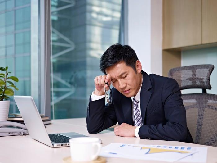 Business man near computer thinking hard
