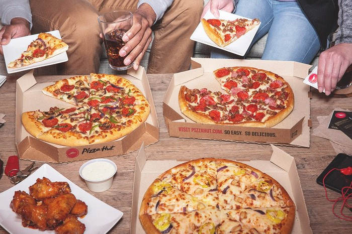 A group of people eating Pizza Hut at home