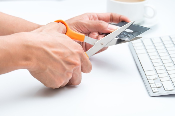 A person cutting a credit card with scissors.