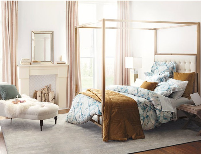 A bedroom set featuring a four-poster bed and a divan