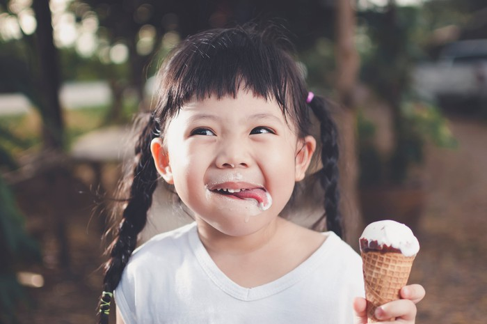 A young, smiling girl in pigtails holds an ice cream cone and smiles as she licks ice cream off her face.