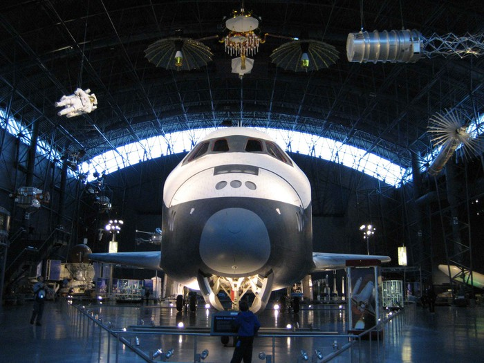 Space Shuttle in a museum, with satellites and other spacecraft hanging from the rafters in a hangar-like building.