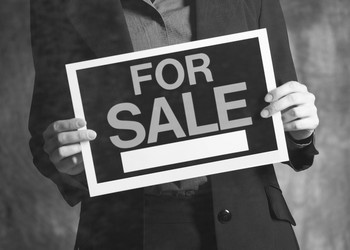 Man Holding For Sale Sign Buyout M&A Getty