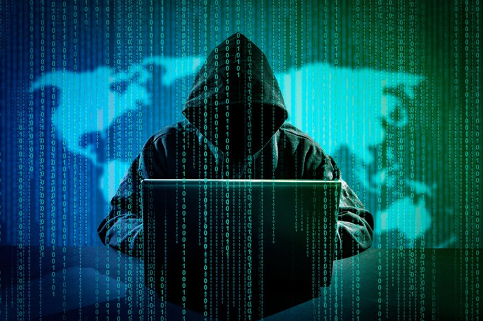 A figure in a dark hood working at a computer against the backdrop of a map of the world with binary numbers running down the screen.