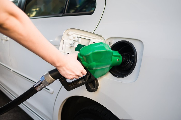A hand holding a green diesel pump to refuel a white vehicle.