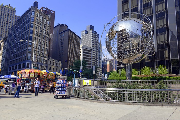 A commercial property complex with street vendors and a metal globe.