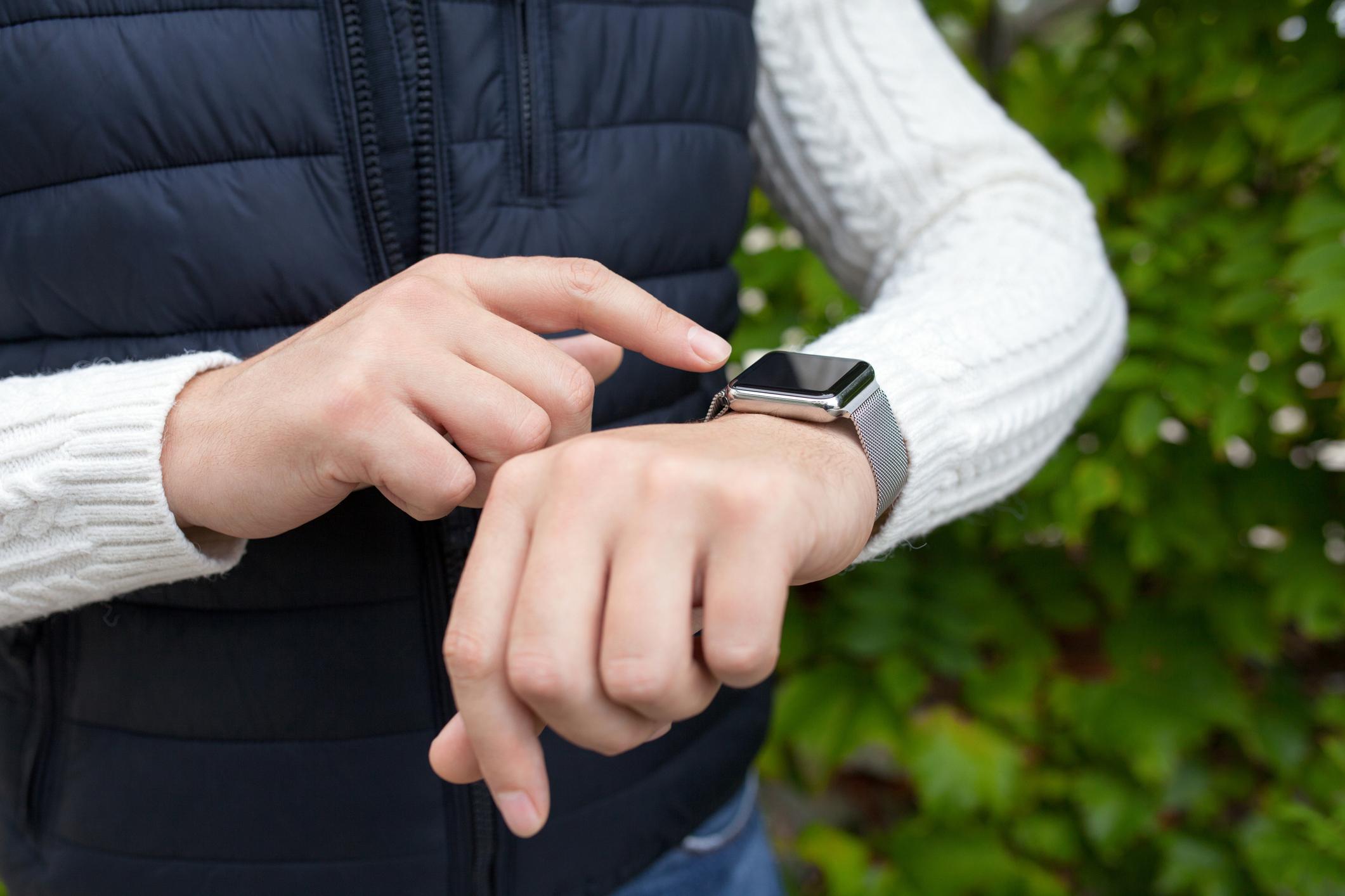 Person wearing a smartwatch outside.