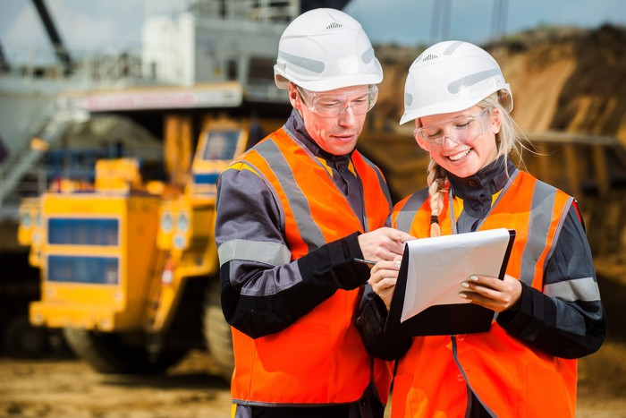 Two people looking at a clip board with mining trucks in the background.