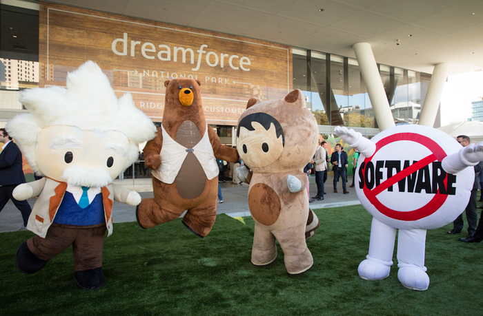 Four different mascots stand in front of a Dreamforce sign during Salesforce's 14th annual conference