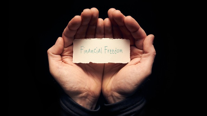 A pair of hands holding a sheet of paper that reads: Financial Freedom