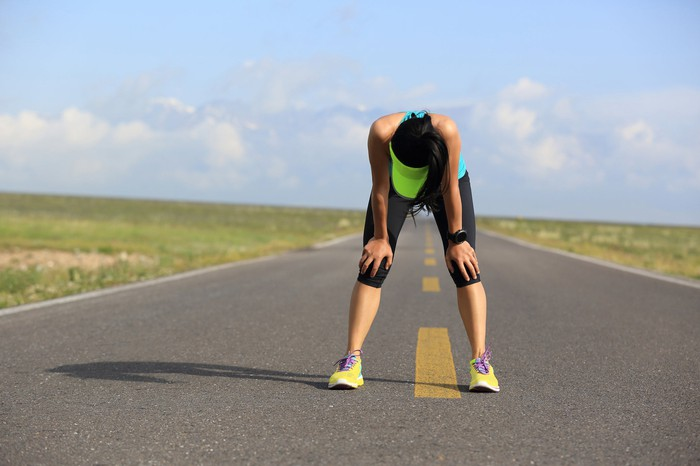 An exhausted runner catching her breath on a road.