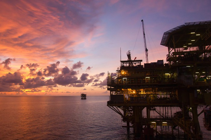 An offshore oil platform at sunset.