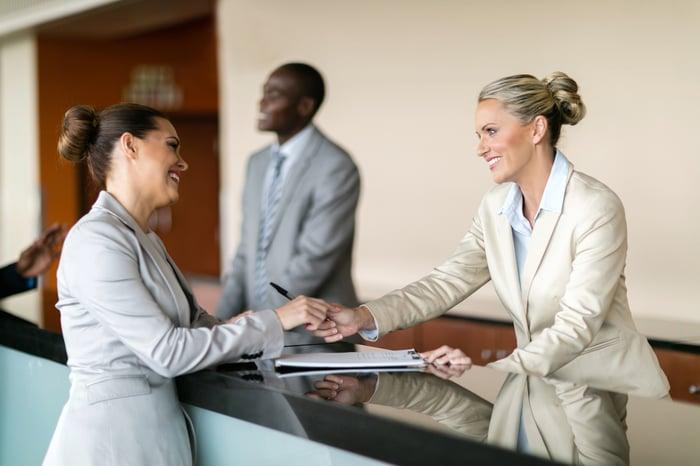 A person checks in at a hotel reception counter.
