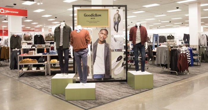An in-store display of one of Target's new brands, Goodfellow and Co. Several men's outfits are displayed in front of a banner with a male model wearing jeans, a white T-shirt, and a sweater jacket.