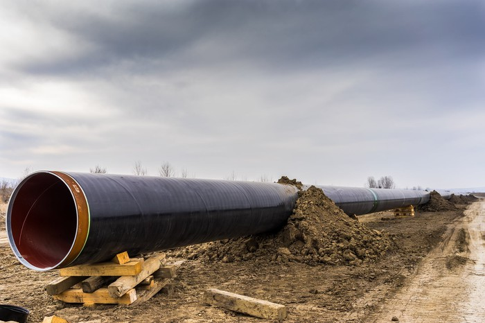 A gas pipeline under construction with a cloudy sky in the background.