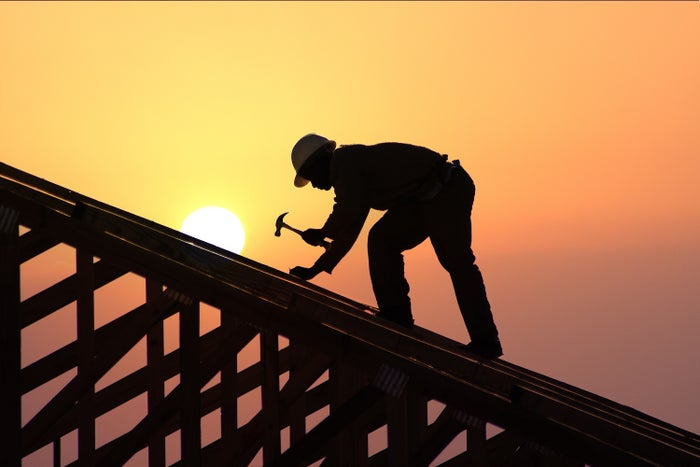 A carpenter working on a house frame.