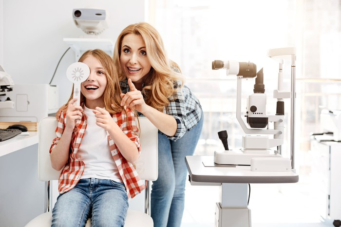 A child and her mother smiling as she gets an eye exam.