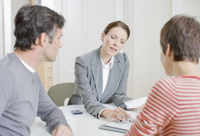 A woman in business attire reviews a document with a couple across the desk.