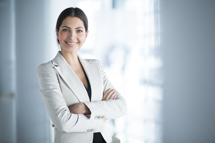 woman in business suit smiling with arms crossed