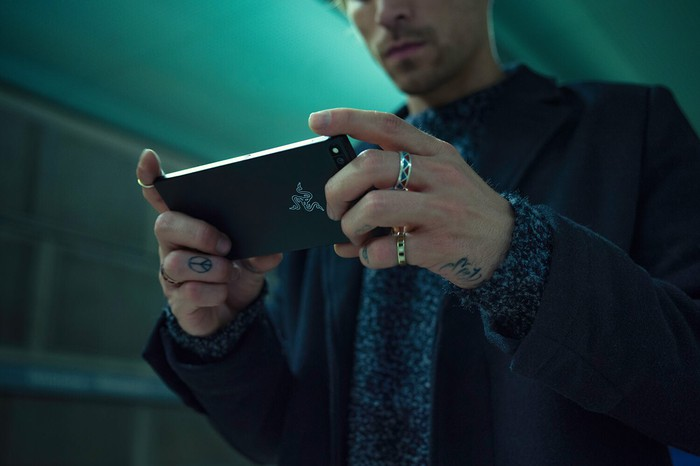 A man holding and looking at the Razer Phone.
