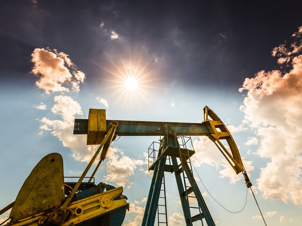 An oil pump with a sunny sky in the background.