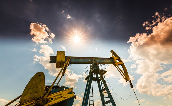 An oil pump with a sunny sky in the background