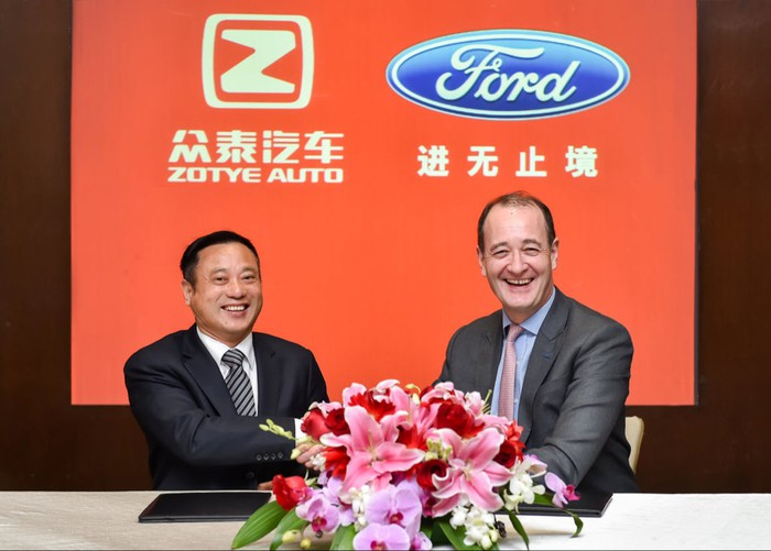 Fleet and Ying are seated at a table in front of a red banner with the Zotye Auto and Ford logos.