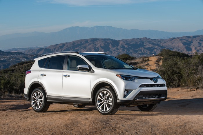 A white Toyota RAV4, a compact SUV, parked with mountains in the background.