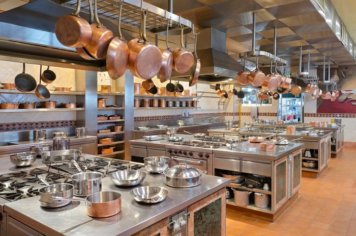 Commercial kitchen with pans hanging from the ceiling and a full array of counters, equipment, stoves, and ovens