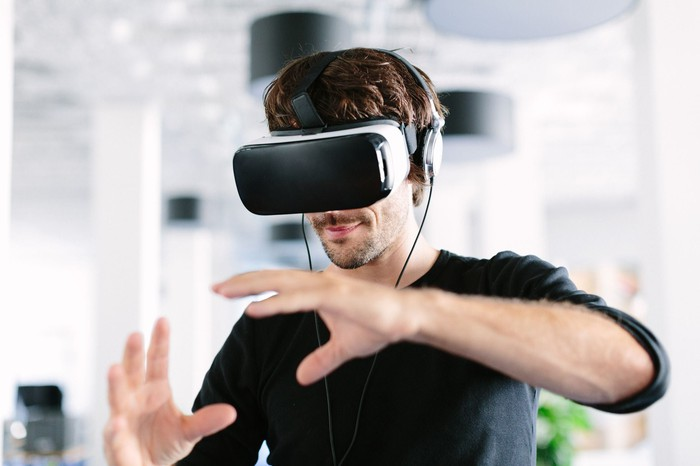 A man interacts with a virtual reality headset