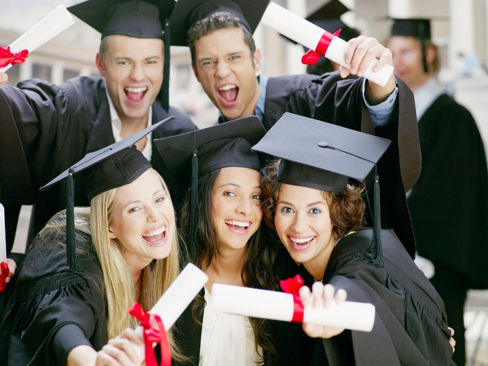 Jubilant college students in caps and gowns holding their college diplomas.