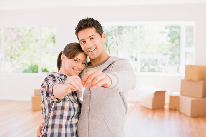A couple holding a key to their new home, with moving boxes in the background.