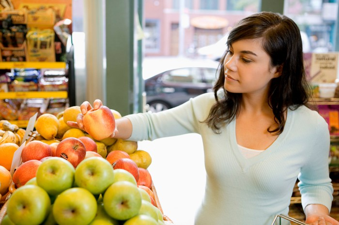 A young woman buying apples.