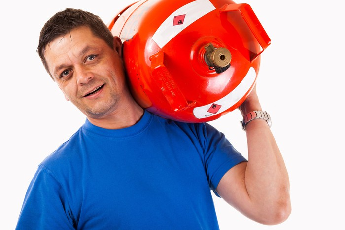 A man with a propane canister on his shoulder