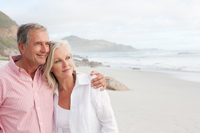 Older couple standing on a beach, facing the water.