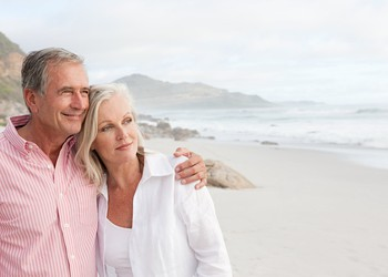 Older couple on beach facing camera