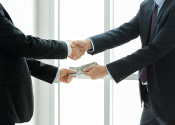 Businessman taking money while shaking hands.