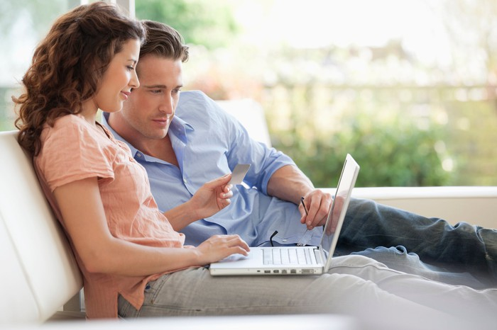A man and woman looking at a computer screen while holding a credit card.