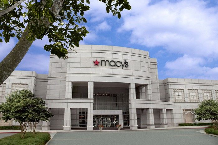 Macy's storefront, in a two-story format with trees in front of the store on a partly-cloudy day.