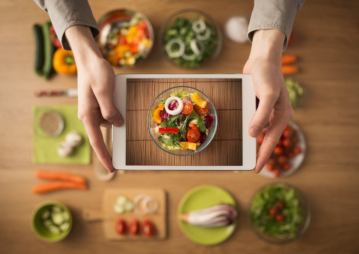 Culinary ingredients spread around wood table, with hands holding a tablet showing the image of the completed dish, a colorful salad.